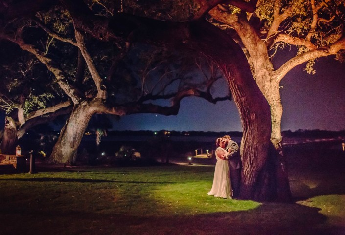 Bride and Groom Kissing Under the Tree