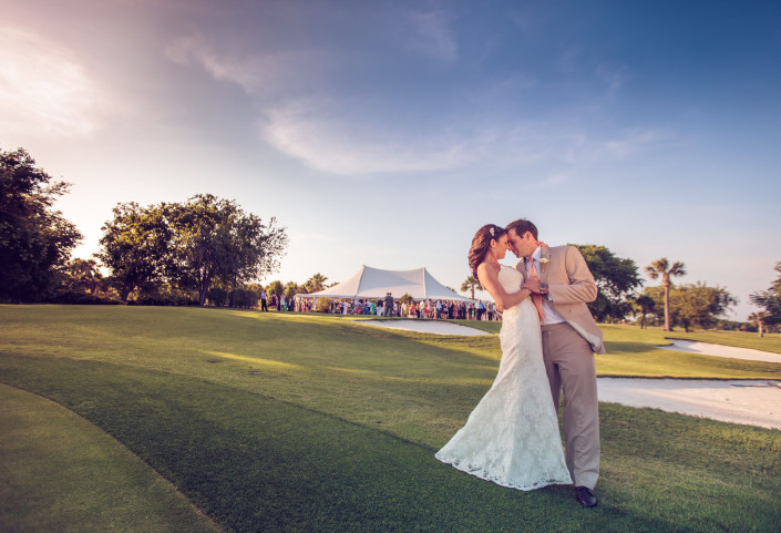 Groom dips bride with tent in the bg